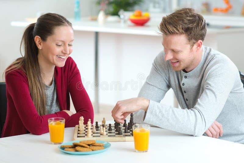 Młoda piękna para grająca w szachy zdjęcia royalty free