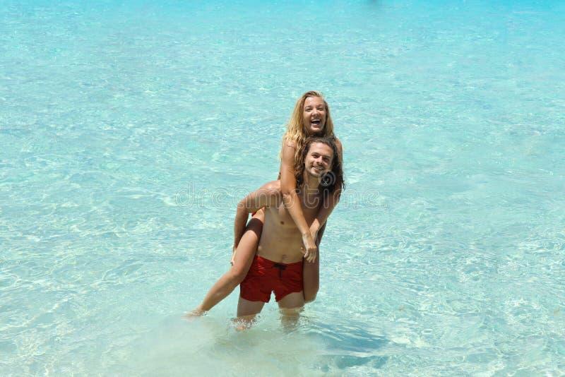 Młoda piękna para ma zabawę wpólnie podróżuje w błękitnym morzu, cieszyć się urlopowy i podróżny, dziewczyny obsiadanie na plecy  zdjęcie stock