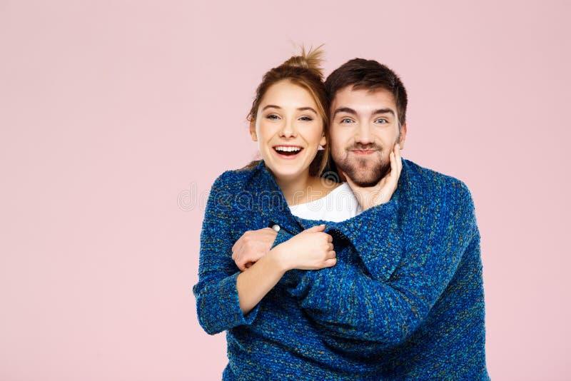 Młoda piękna para w jeden błękitnym trykotowym pulowerze pozuje uśmiecha się mieć zabawę nad światłem - różowy tło zdjęcie royalty free