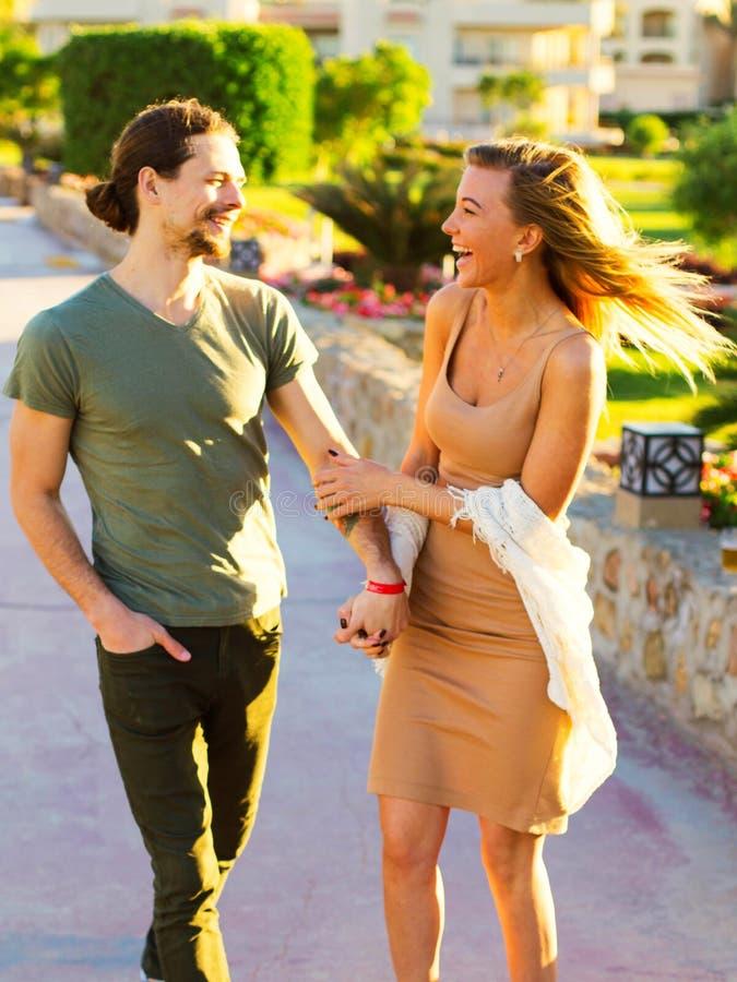 Młoda piękna para w miłości trzyma ręki, romantyczny odprowadzenie na wakacyjnym outside, mieć datę, patrzejący innych oczy each, obraz royalty free