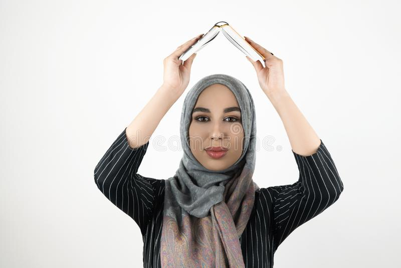 Młoda piękna pełny nadziei Muzułmańska kobieta jest ubranym turbanu hijab, chustki na głowę mienia książka w ona ręka koszt stały obrazy royalty free