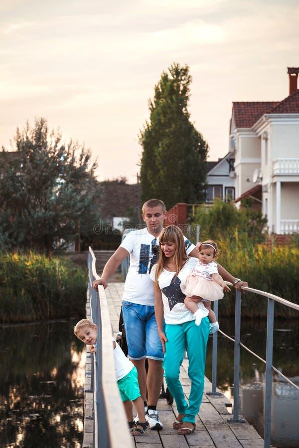 Młoda piękna rodzina przy mostem, ojciec, matka i dzieciaki, iść z powrotem do domu od outside zdjęcia stock