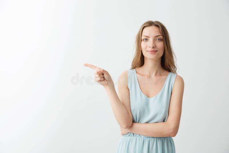 Młoda piękna rozochocona dziewczyna ono uśmiecha się patrzejący kamerę wskazuje palec w stronie nad białym backrgound zdjęcia stock