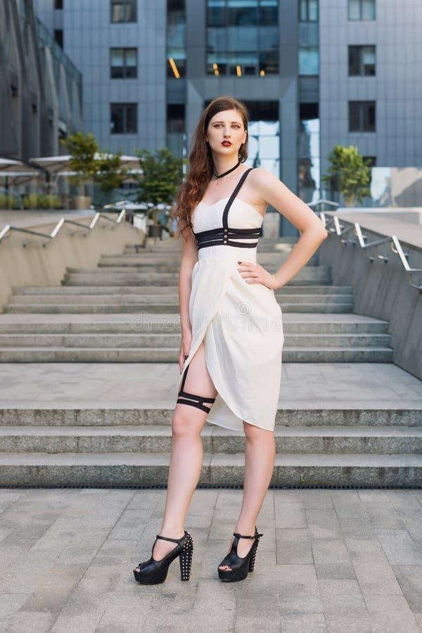 Młoda piękna seksowna kobieta jest ubranym modnego strój, bielu swordbelt, smokingowego i rzemiennego Longhaired brunetka pozuje  obrazy royalty free
