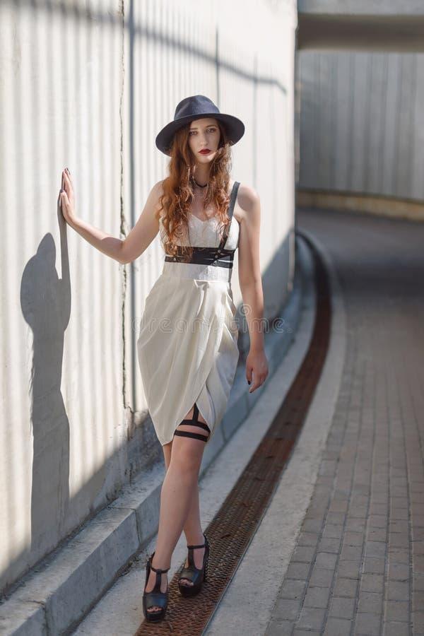 Młoda piękna seksowna kobieta jest ubranym modnego stroju, biel sukni, czarnego kapeluszu i skóry swordbelt, Longhaired brunetka zdjęcie stock