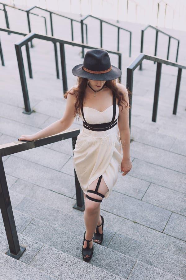 Młoda piękna seksowna kobieta jest ubranym modnego stroju, biel sukni, czarnego kapeluszu i skóry swordbelt, Longhaired brunetka obraz royalty free