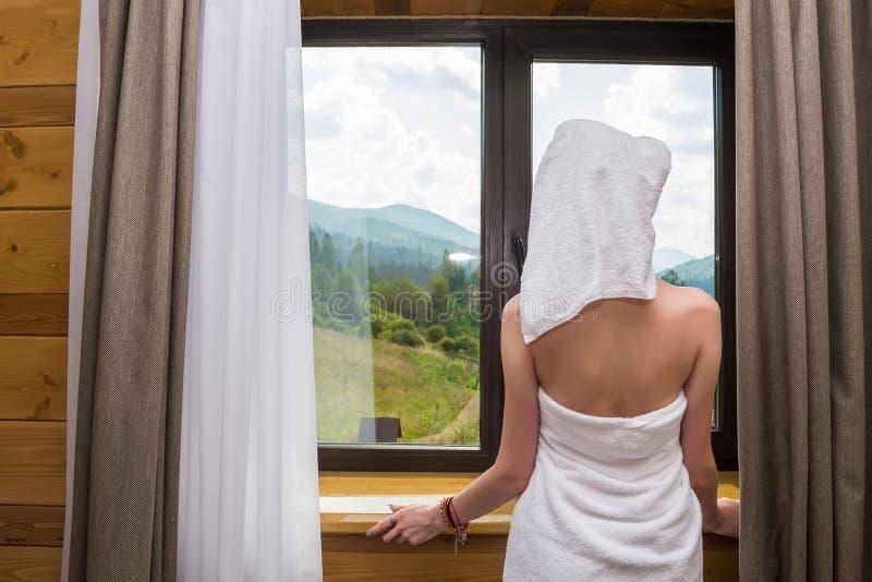 Młoda, piękna, seksowna kobieta, po tym jak prysznic, stojaki zawijający w ręczniku blisko okno w hotelu z widokiem góry obrazy stock