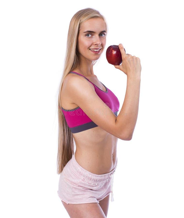 Młoda piękna seksowna kobieta w sportswear z czerwonym jabłkiem zdjęcia stock