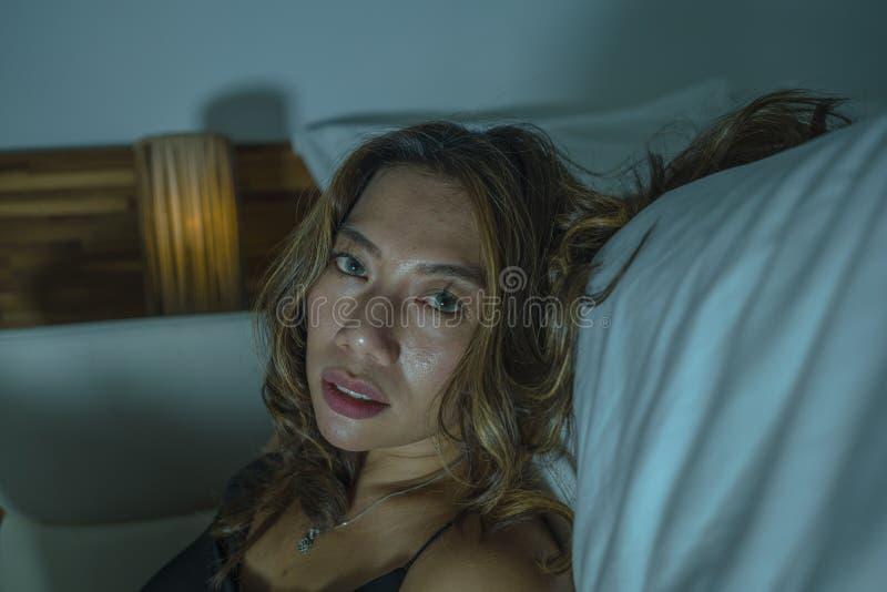 Młoda piękna smutna, przygnębiona Azjatycka Indonezyjska kobieta w koszula nocnej na sypialni podłodze łóżkowym uczuciem i fotografia royalty free