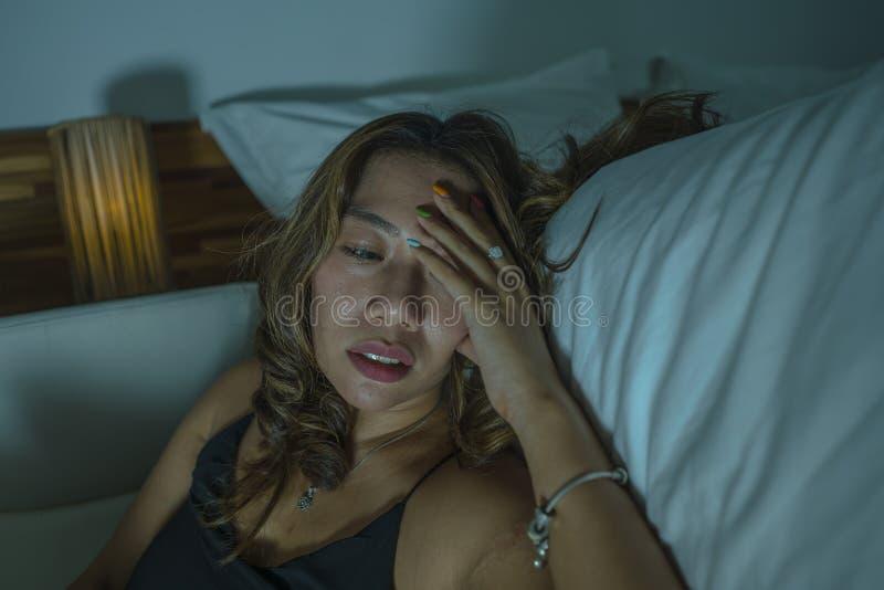 Młoda piękna smutna, przygnębiona Azjatycka Indonezyjska kobieta w koszula nocnej na sypialni podłodze łóżkowym uczuciem i obrazy stock