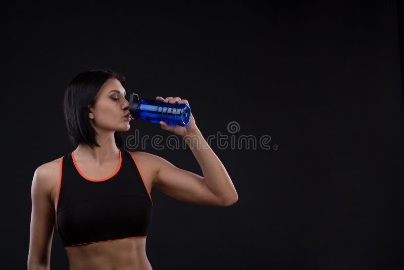 Młoda piękna sportive dziewczyny woda pitna nad czarnym tłem zdjęcie royalty free