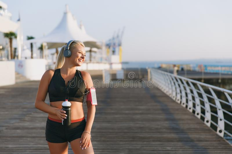 Młoda piękna sportowa dziewczyna z długim blondynem w hełmofonach i butelce woda w ręk spojrzeniach przy morzem przy świtem obraz stock