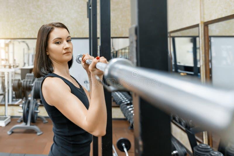 Młoda piękna sportowa kobiety brunetka robi sprawności fizycznej ćwiczy w gym Sprawność fizyczna, sport, szkolenie, ludzie, zdrow fotografia stock
