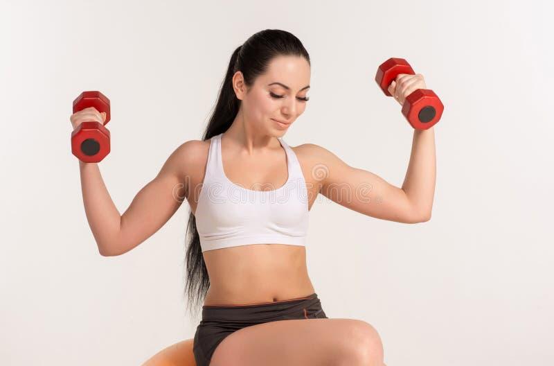 Młoda piękna sportsmenka ćwiczy na fitball z dumbbells fotografia stock
