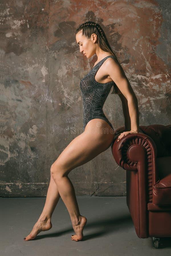 Młoda piękna sporty dziewczyna w luksusowym swimsuit ciele pozuje opierać przeciw kanapy Vertical składowi Odprężny napad fotografia royalty free