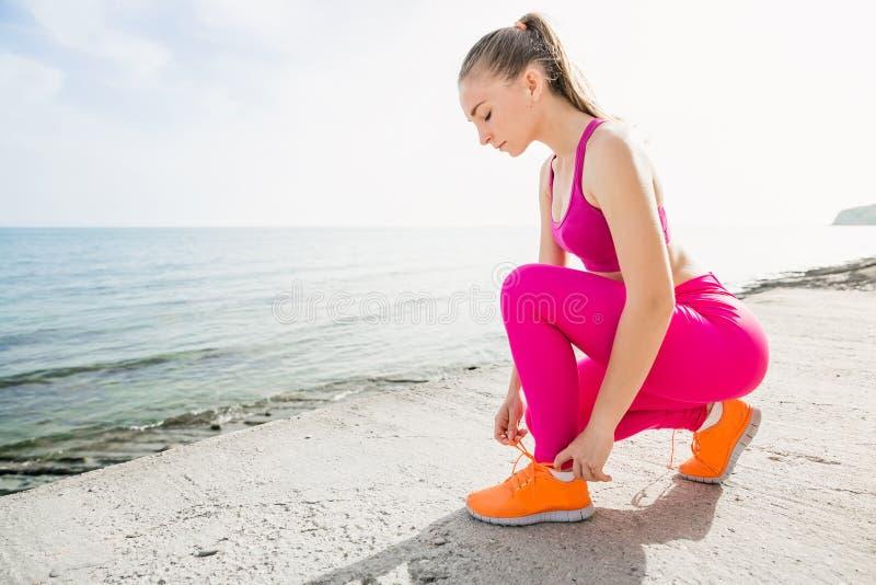 Młoda piękna sporty dziewczyna w menchiach munduruje na morzu Wiąże shoelaces obrazy stock