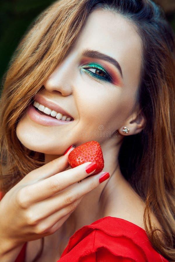 Młoda piękna szczęśliwa śmieszna dziewczyna z czerwieni sukni i makeup mienia truskawką w lecie w parku zdjęcia royalty free