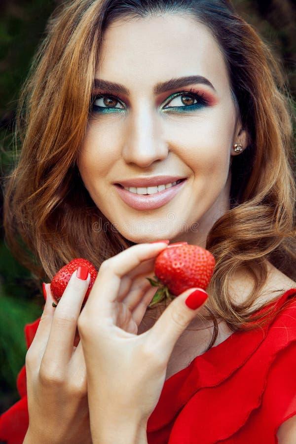 Młoda piękna szczęśliwa śmieszna dziewczyna z czerwieni sukni i makeup mienia truskawką w lecie w parku fotografia royalty free