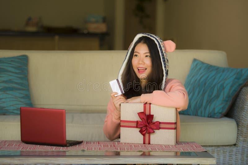Młoda piękna, szczęśliwa Azjatycka Chińska kobieta w zimy hoodie mienia karcie kredytowej i zdjęcia stock
