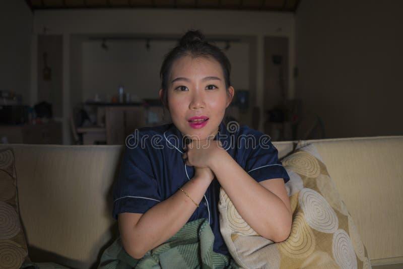 Młoda piękna szczęśliwa i zrelaksowana Azjatycka Chińska kobieta żyje izbowy siedzący wygodnego na kanapy leżanki dopatrywania pr zdjęcia royalty free