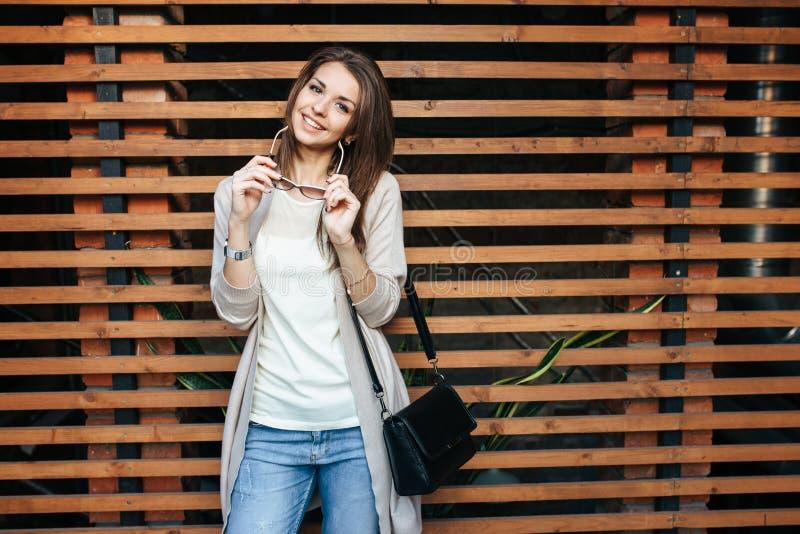 Młoda piękna szczęśliwa kobieta w przypadkowych płótnach przeciw ścianie zdjęcia stock