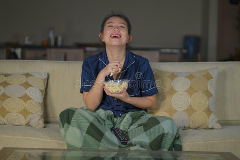 Młoda piękna szczęśliwa, rozochocona Azjatycka Koreańska kobieta ogląda i TV komediowego film śmia się popkorn i je obraz royalty free