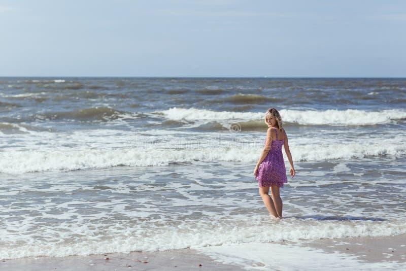 Młoda piękna szczupła dziewczyny pozycja na plaży na pogodnym letnim dniu, silny wiatr na morzu fotografia royalty free