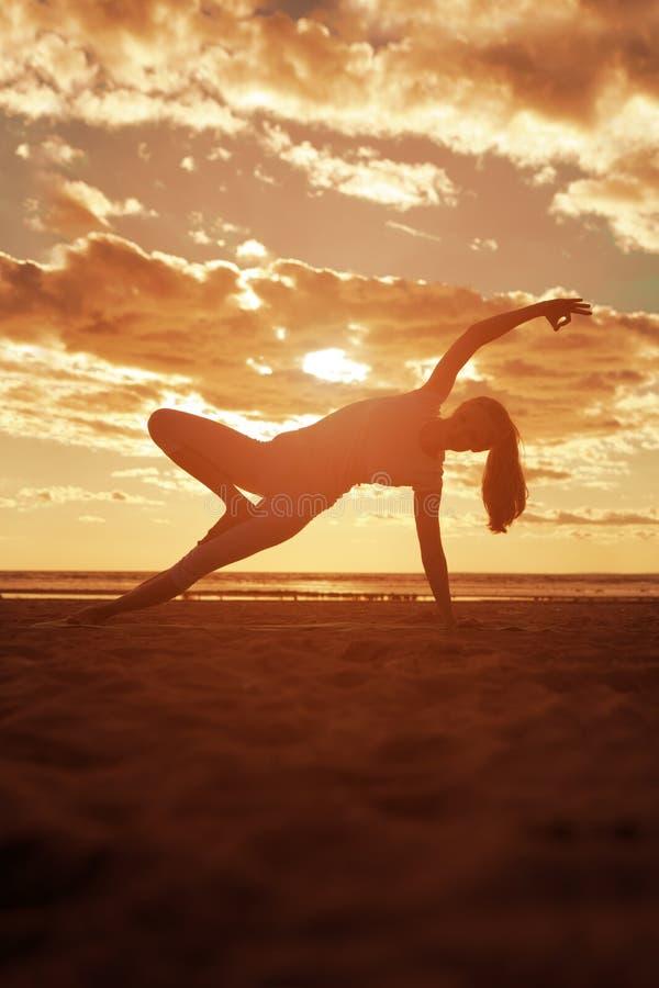 Młoda piękna szczupła kobiety sylwetka ćwiczy joga na beac obrazy stock