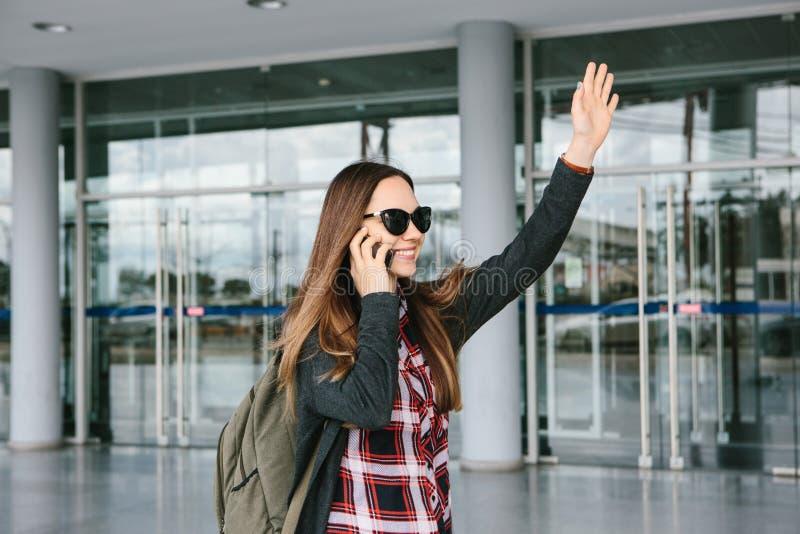 Młoda piękna turystyczna dziewczyna przy lotniskiem lub blisko centrum handlowego lub staci dzwoni taxi lub opowiadać na komórce obraz royalty free