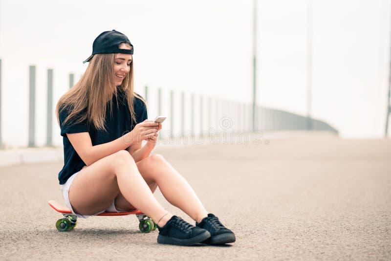 Młoda Piękna Uśmiechnięta blondynki dziewczyna Używa Smartphone podczas gdy Siedzący na deskorolka obraz royalty free