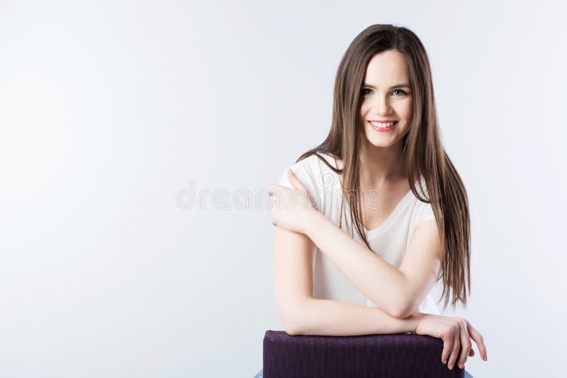 Młoda piękna uśmiechnięta kobieta z długim prostym włosy na szarości zdjęcie royalty free