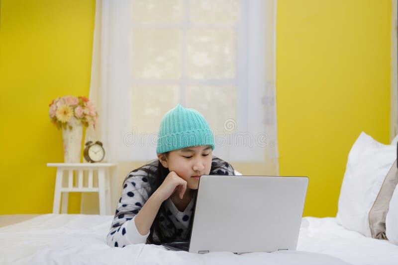 Młoda piękna uśmiechnięta nastoletnia dziewczyna używa laptop zdjęcia stock