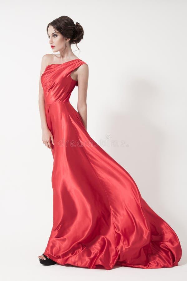 Młoda piękno kobieta w trzepotliwej czerwieni sukni. Biały tło. obrazy royalty free