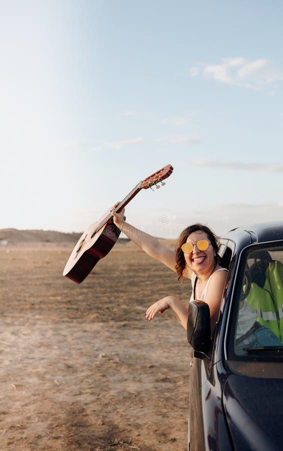 Młoda podróżnik kobieta ma zabawę z gitarą w dżipa 4x4 samochodzie robi podróżomania wakacje przy zmierzchem zdjęcia stock