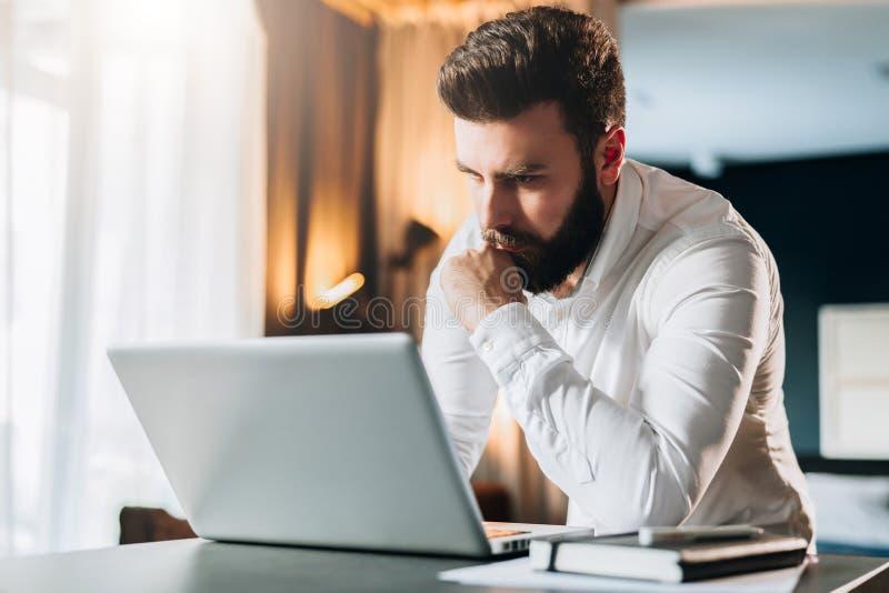 Młoda poważna brodata biznesmen pozycja w biurowym pobliskim stole i używać laptopie Mężczyzna pracy na komputerze, czeki e-mailo obraz stock