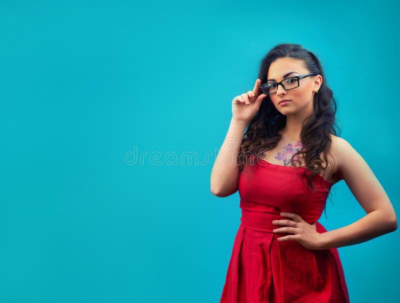 Młoda poważna dziewczyna z makeup, będący ubranym szkła i czerwieni suknię obraz stock