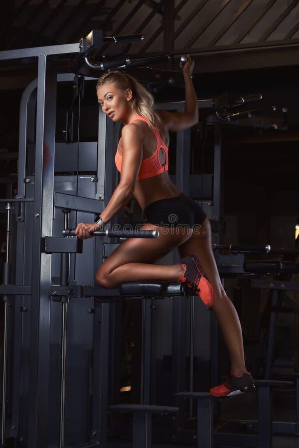 Młoda powabna blondynki kobieta w sportswear pozuje na graviton maszynie w nowożytnym sprawności fizycznej centrum zdjęcie stock