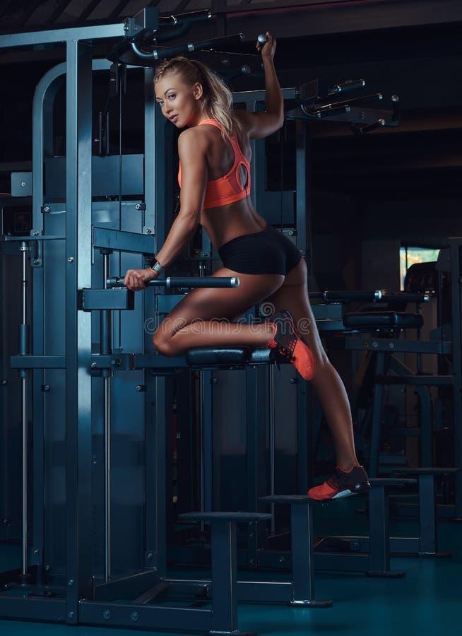 Młoda powabna blondynki kobieta w sportswear pozuje na graviton maszynie w nowożytnym sprawności fizycznej centrum obrazy stock