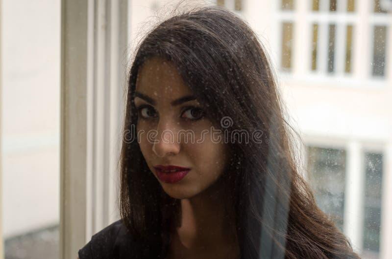Młoda powabna brunetki dziewczyna za szklanym okno obraz stock