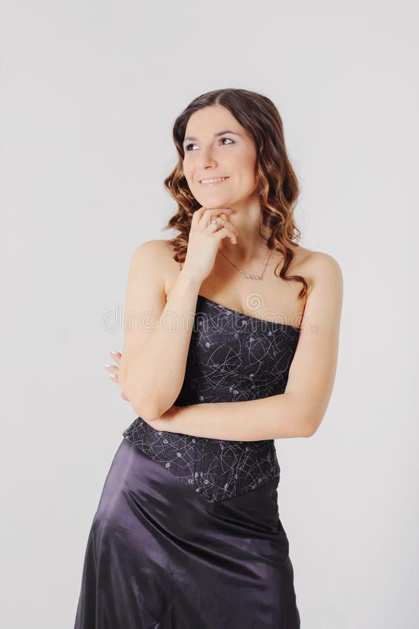 Młoda powabna brunetki kobieta z kędzierzawym włosianym stylem w wieczór e obraz royalty free