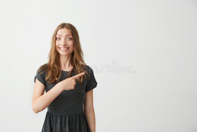 Młoda pozytywna ładna dziewczyna ono uśmiecha się patrzejący kamerę wskazuje palec w stronie nad białym tłem obraz royalty free