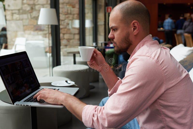 Młoda przedsiębiorca praca na netbook trzyma filiżankę herbata lub kawiarnia podczas gdy on siedzi w nowożytnym sklep z kawą zdjęcie stock