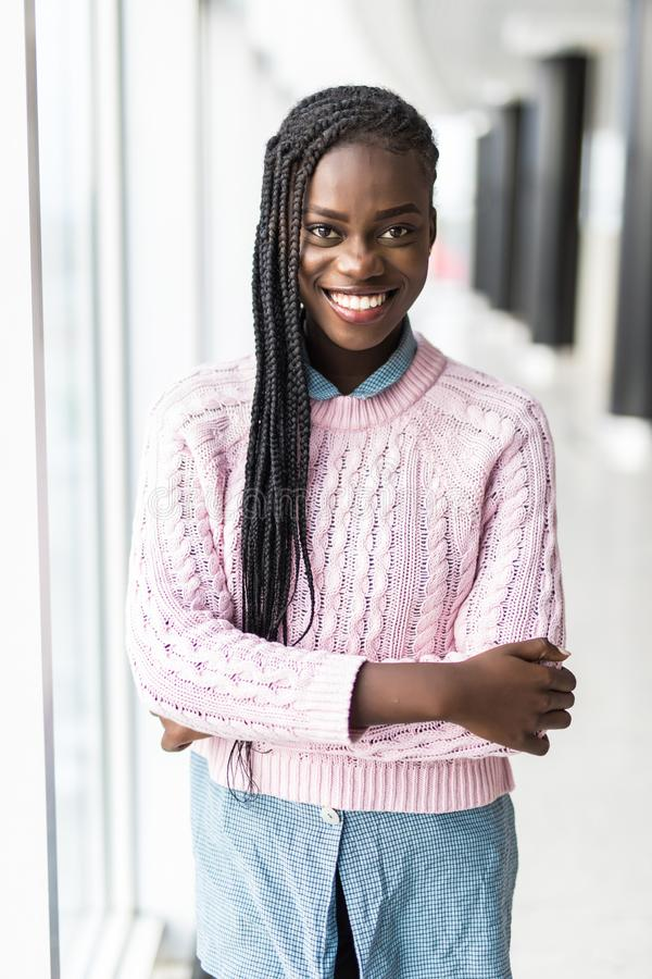 Młoda przypadkowa afro amerykańska kobiety pozycja przed panoramicznym okno w nowożytnym centrum biznesu obrazy stock