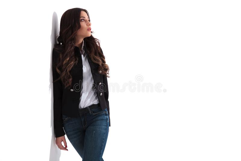 Młoda przypadkowa kobieta opiera na biel ścianie marzy daleko od zdjęcia stock