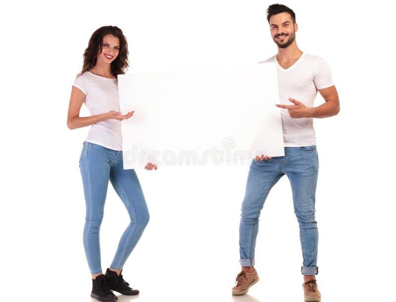 Młoda przypadkowa para wskazuje pusta deska zdjęcia royalty free