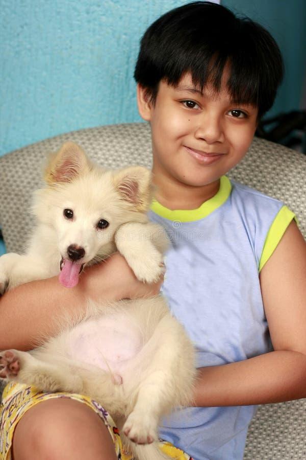Młoda przystojna Azjatycka chłopiec niesie ślicznego białego szczeniaka fotografia stock