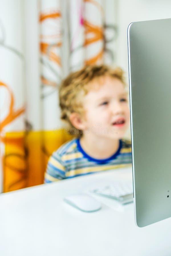 Młoda przystojna chłopiec ogląda na ekranie komputerowym zdjęcia stock