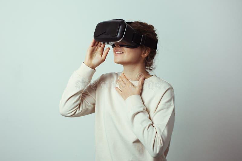 Młoda przystojna kobieta jest ubranym wirtualną słuchawki Z podnieceniem modniś używa VR szkła Pusty studio ściany tło zdjęcia royalty free
