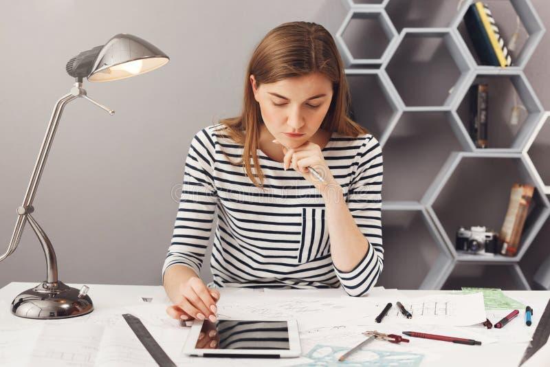 Młoda przystojna poważna inżynier dziewczyna z długim brown włosy w pasiastej koszulowej mienie głowie z ręką, patrzeje w papiera obraz stock