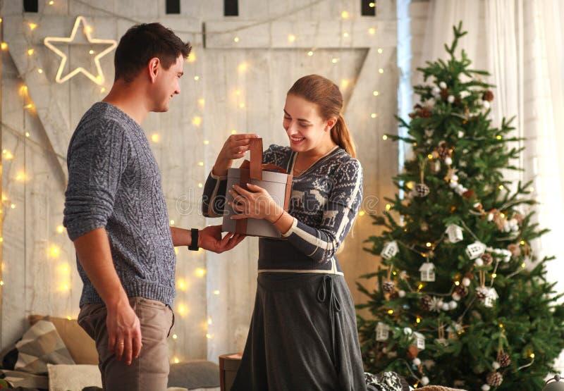Młoda radosna para daje teraźniejszość przy boże narodzenie nowym rokiem w domu obrazy royalty free